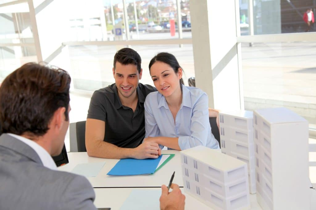 Couple In Real Estate Agency Signing Property
