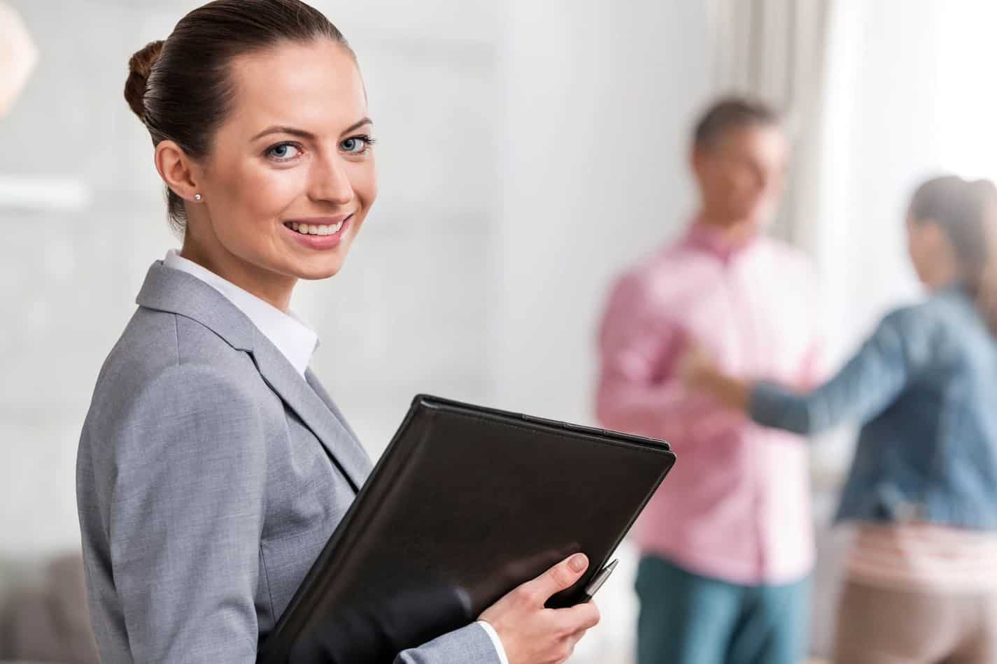 Portrait Of Smiling Young Female Realtor Holding Document With Clients In Background