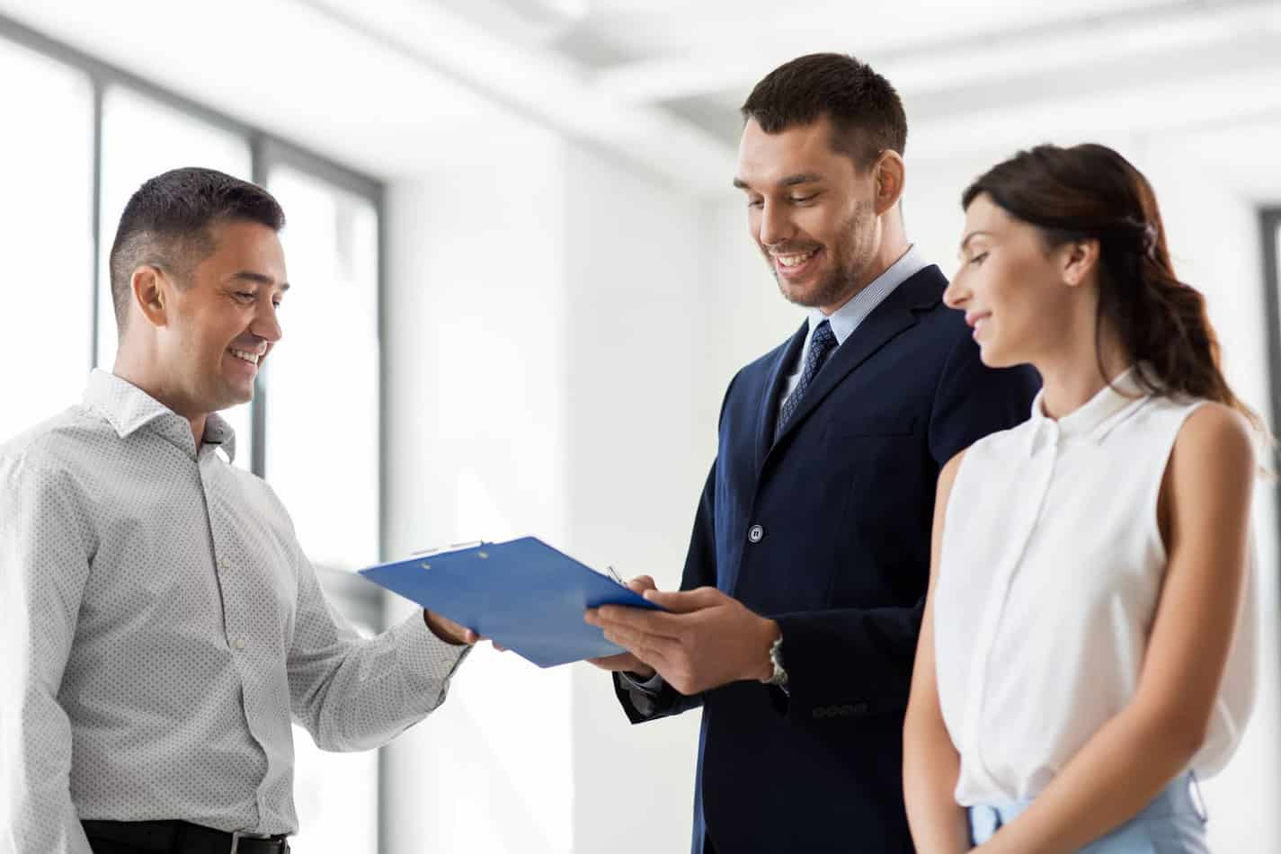 Real Estate Business Sale And People Concept Male Realtor With Clipboard And Pen Showing Contract Document To Customers At New Office Room Realtor