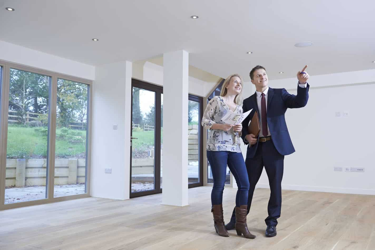Real Estate Agent Showing Prospective Female Buyer Around Property