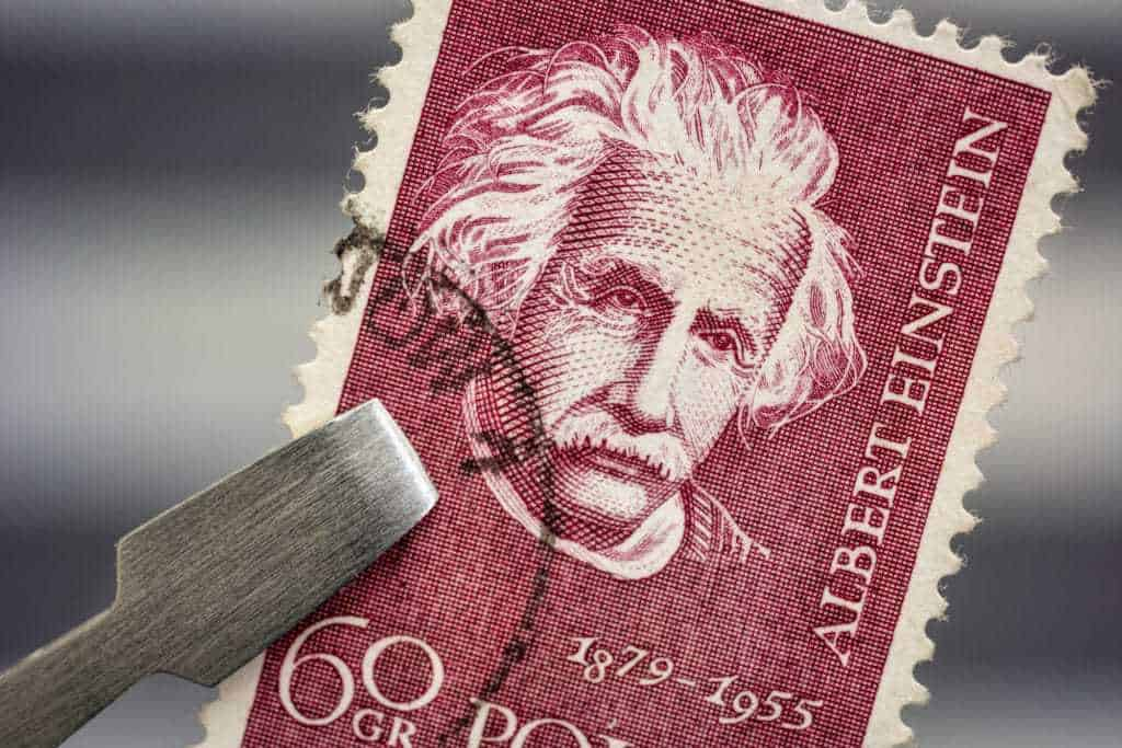 Albert Einstein Portrait On A Vintage Canceled Post Stamp From Poland Held By Tweezer Above A Page Of Stamp Album