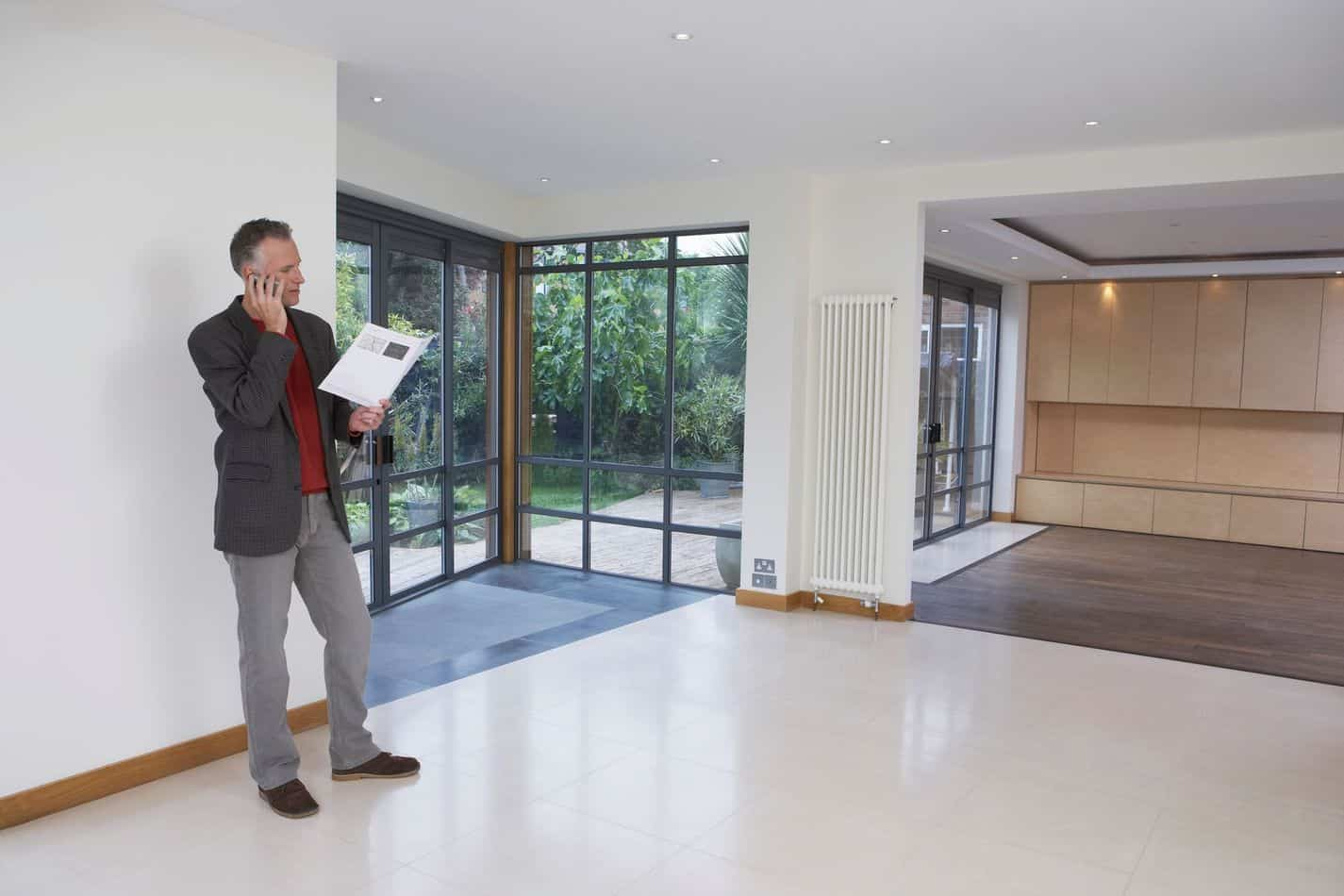 Real Estate Agent Using Mobile Phone In New Property
