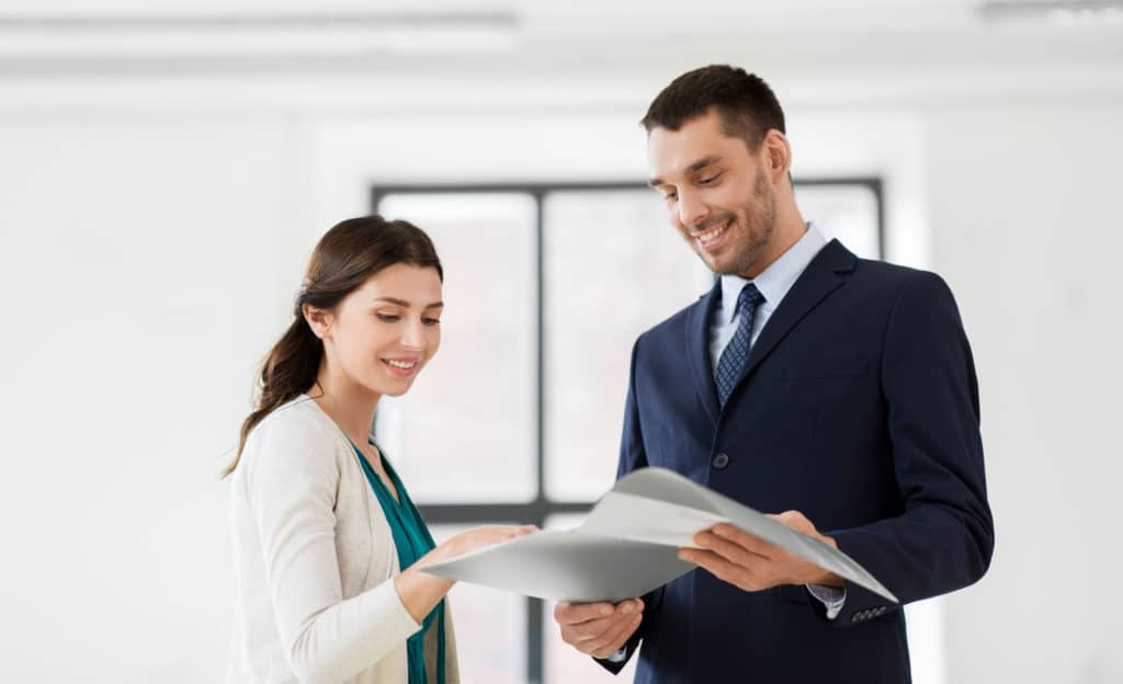 Real Estate Business Sale And People Concept Happy Smiling Realtor With Folder Showing Documents To Female Customer At New Office Room Realtor Wit