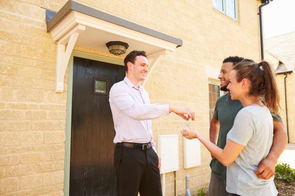 property manager giving key to home buyers