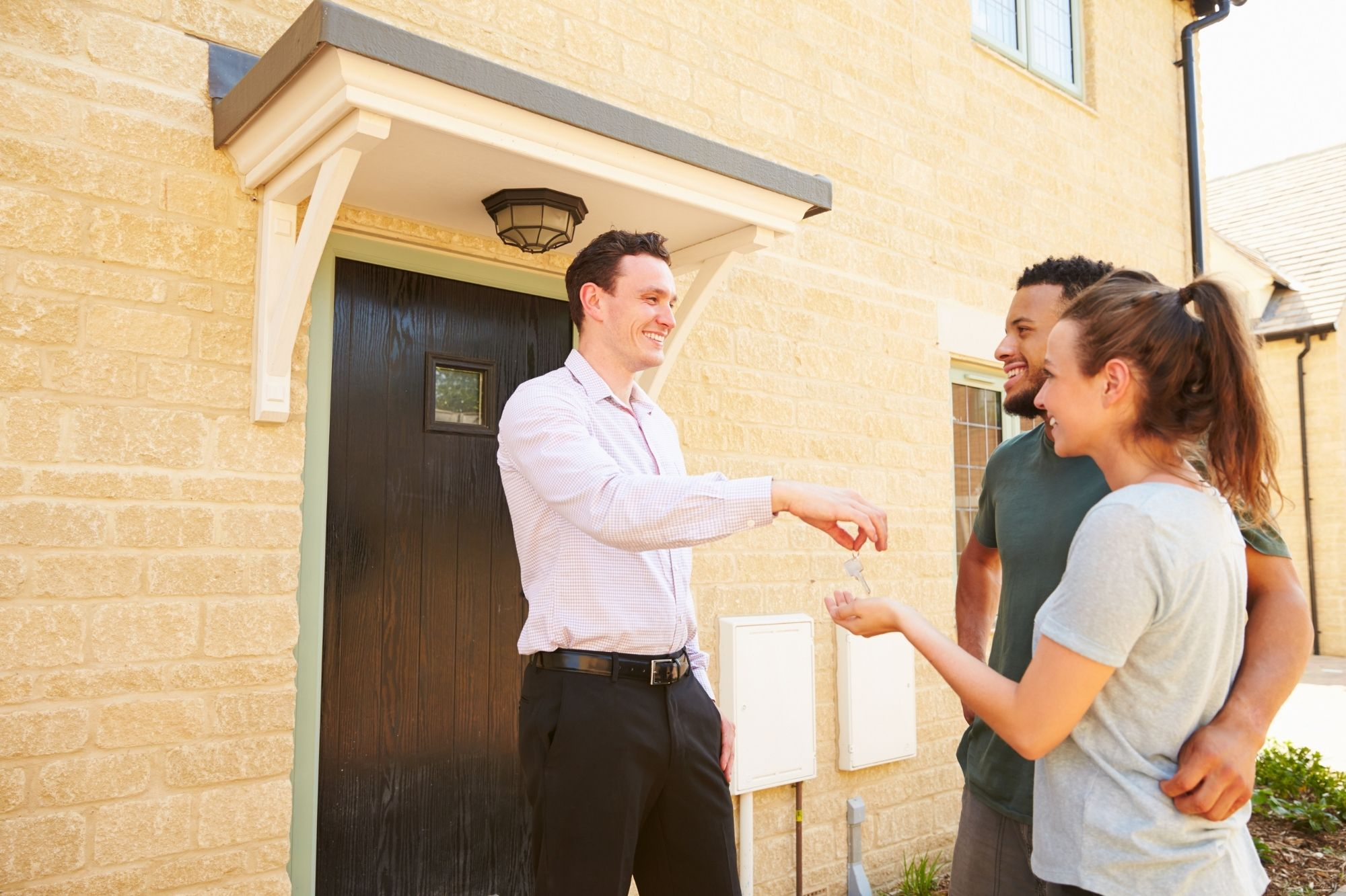 real estate agent giving key to home buyers