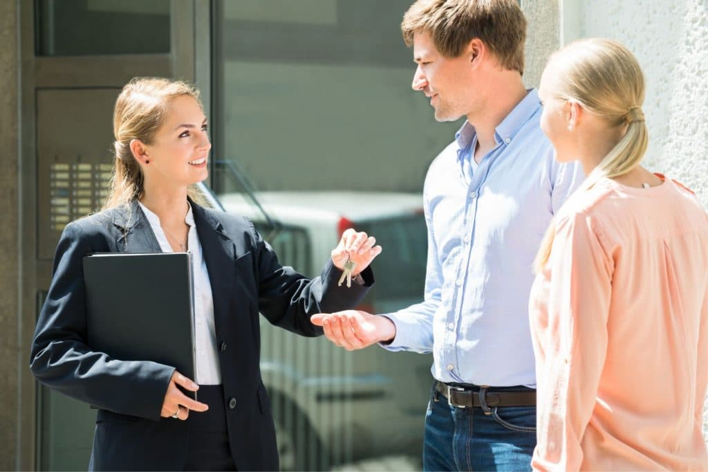 Real estate agent handling out keys to home owners