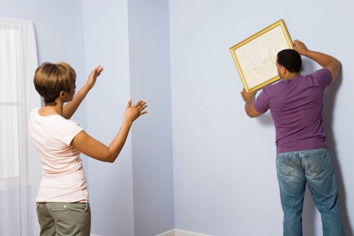 home stager hanging wall painting